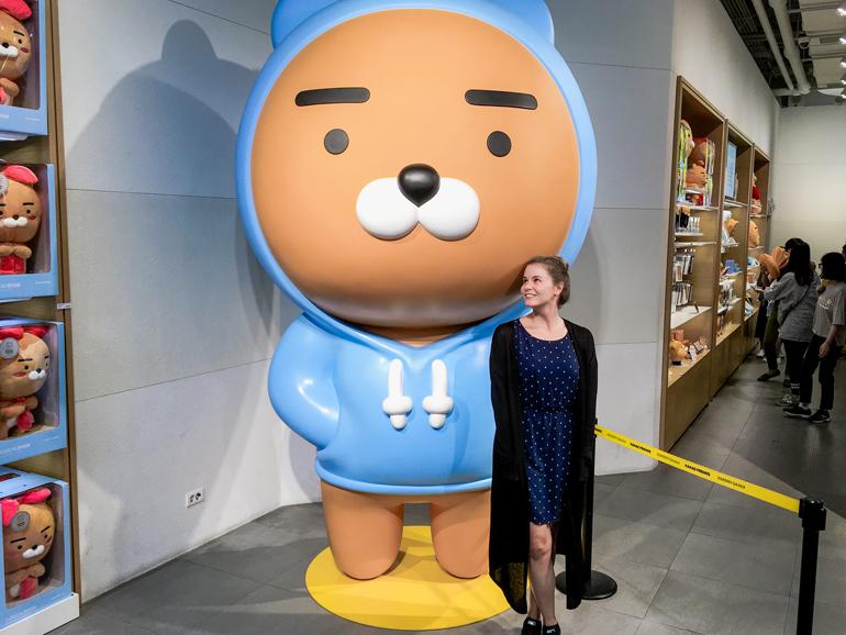 Seoul Sehenswürdigkeiten: Im Kakao Friends Store in Seoul steht eine Frau neben einem riesigen Bären.
