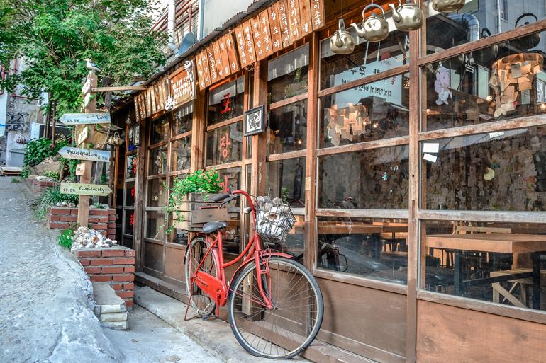 Seoul Sehenswürdigkeiten: In einem Holzhaus befindet sich ein Restaurant, davor lehnt ein rotes Fahrrad.