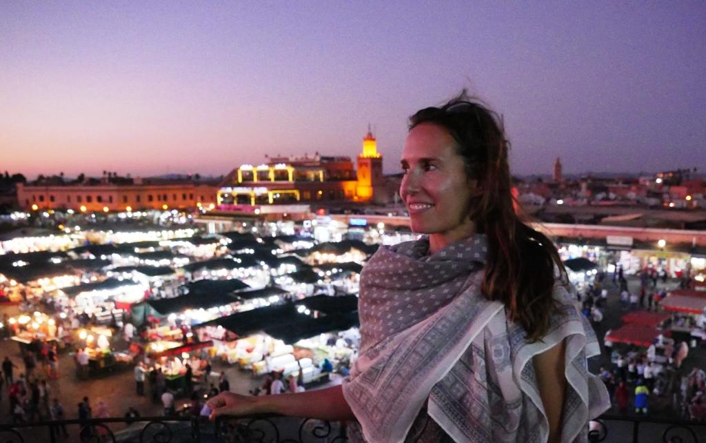 Eine Frau auf Reisen steht allein vor der Skyline Marrakeschs: Sie trägt einen Schal, den Sarong.