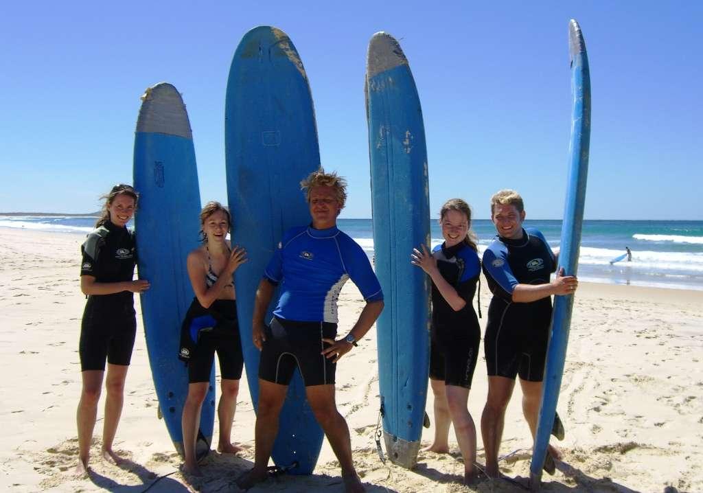 In einem Surfcamp stehen fünf jungen Menschen mit Surfbrettern beieinander am Strand.