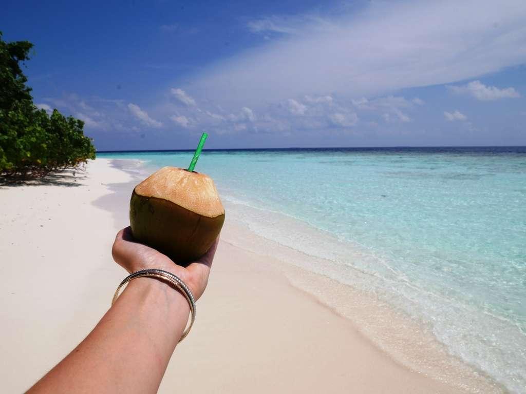 Sich auf Reisen allein einmal so richtig verwöhnen - zum Beispiel mit einem Strohhalm in der Kokosnuss am Strand.