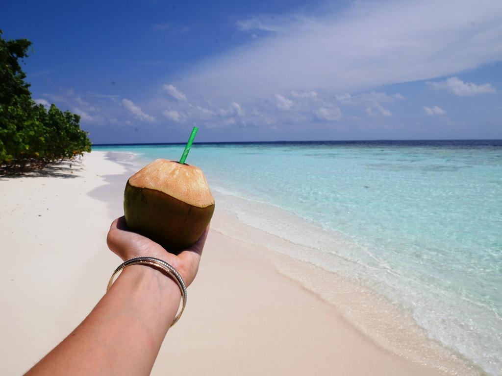 Eine Hand hält eine Kokosnuss mit Strohhalm Richtung Meer.