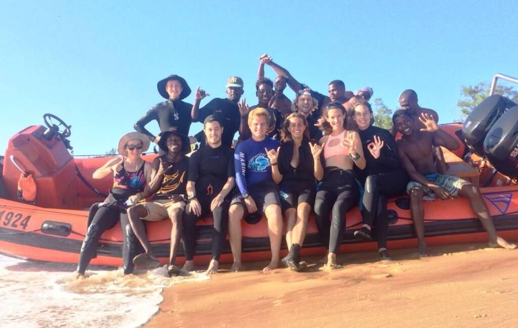In einem Surfcamp sitzt eine Gruppe junger Menschen zusammen auf einem Boot; schnell neue Leute beim Solo Travel kennenlernen klappt in Camps besonders gut.