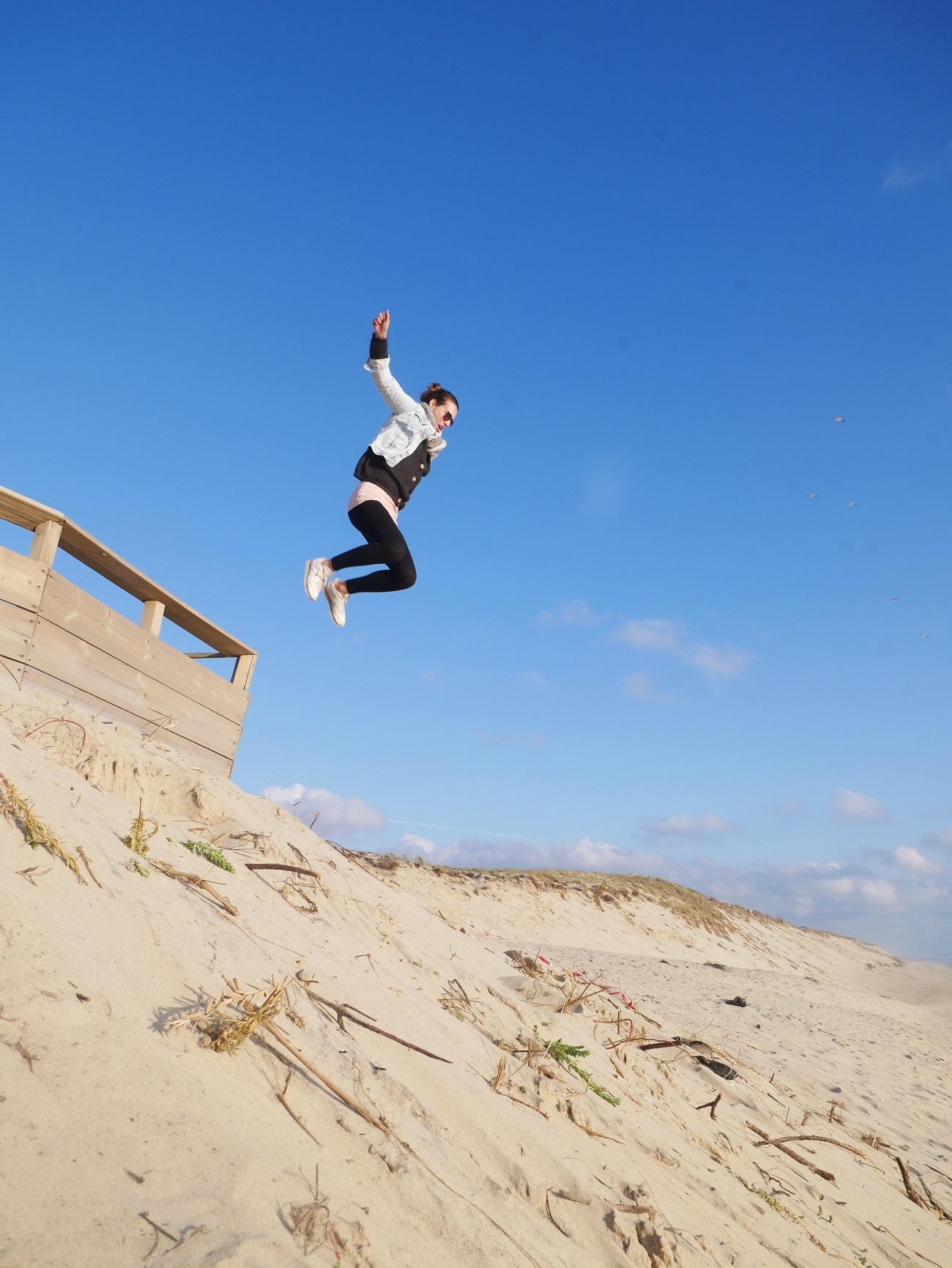Eine Frau springt an einem Strand von einem Holzkonstrukt.