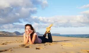 Eine Frau auf Reisen allein am Strand liegend.