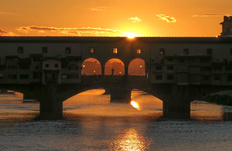 Florenz Geheimtipps: Eine Brücke über einem Fluss im Sonnenuntergang.