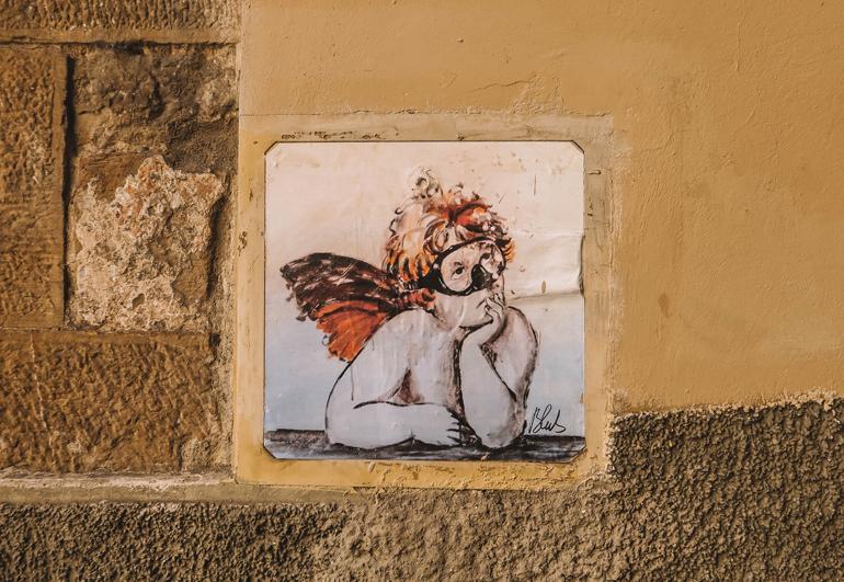 Florenz Geheimtipps: Eine Fliese in einer Mauer mit einem Engel darauf.