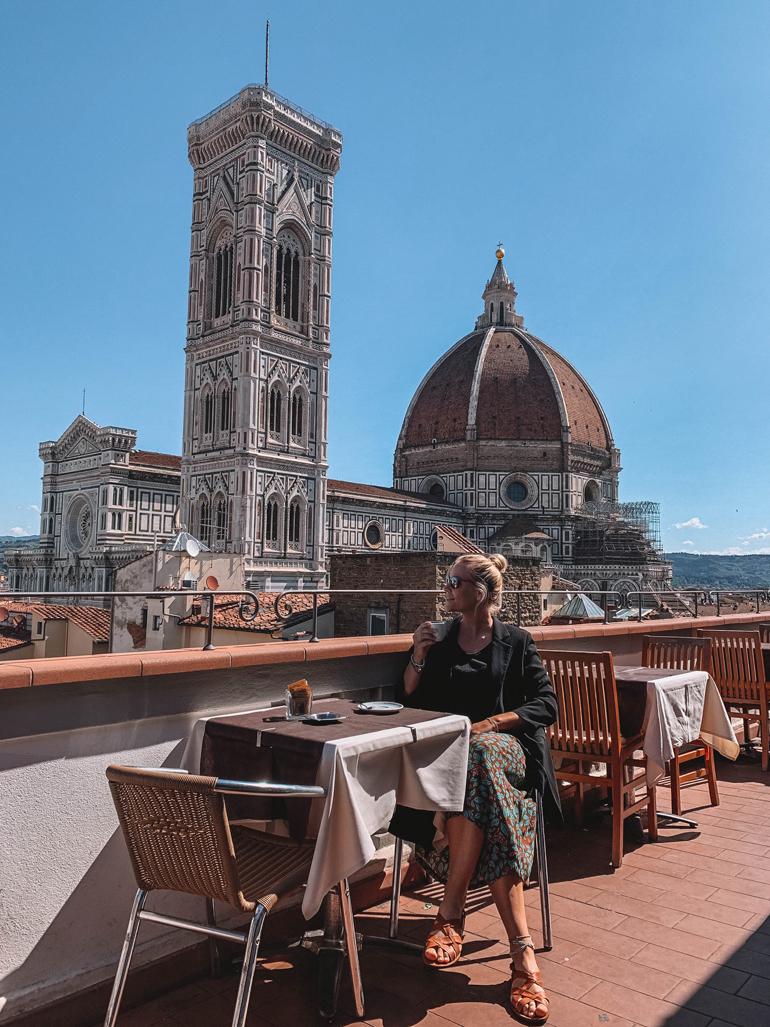 Florenz Geheimtipps: Eine Frau sitzt auf einer Dachterrasse, im Hintergrund eine Kirche.