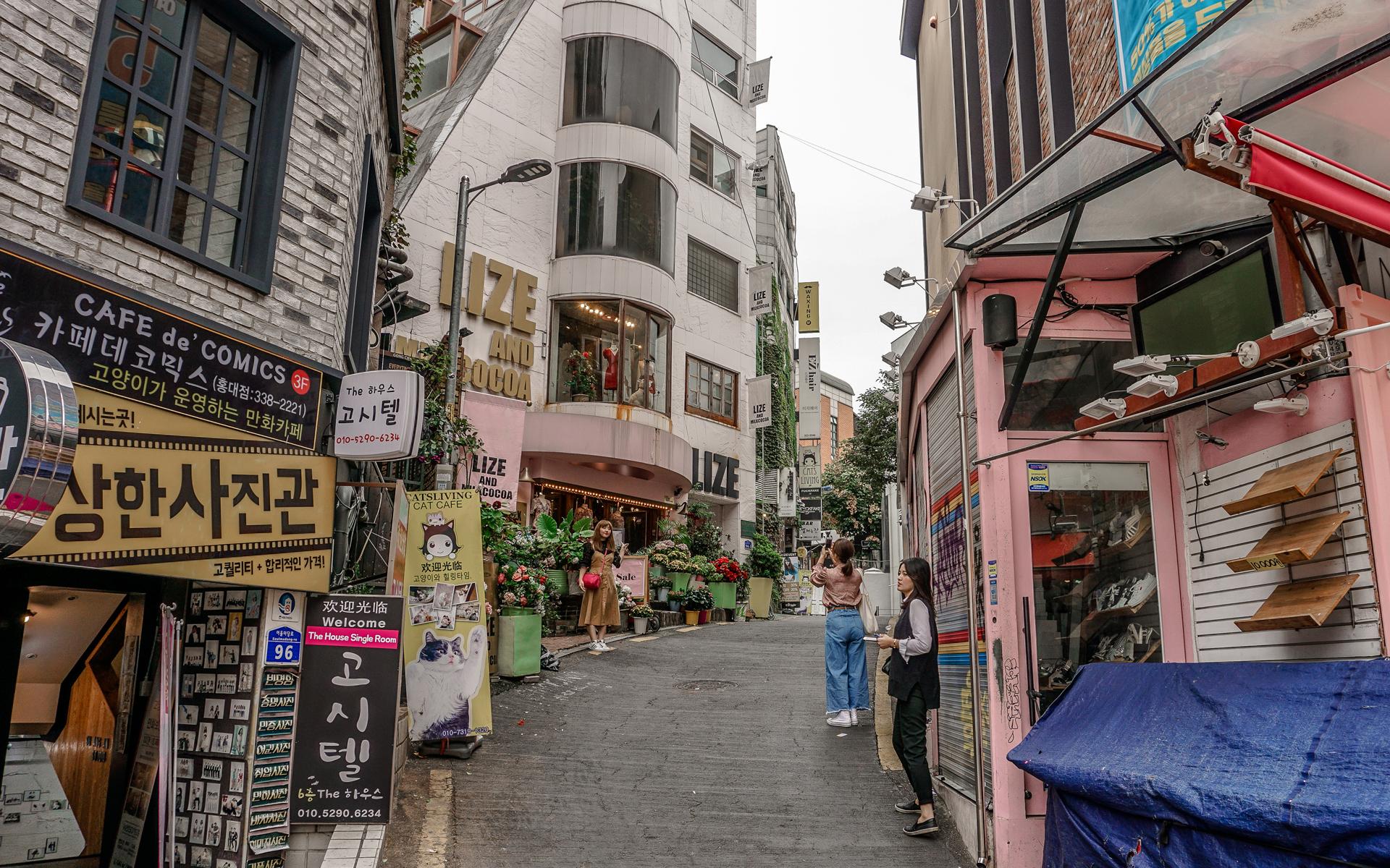 Sehenswüdigkeiten: Eine hippe Gasse in der Innenstadt von Seoul, eine Frau lässt sich fotografieren.