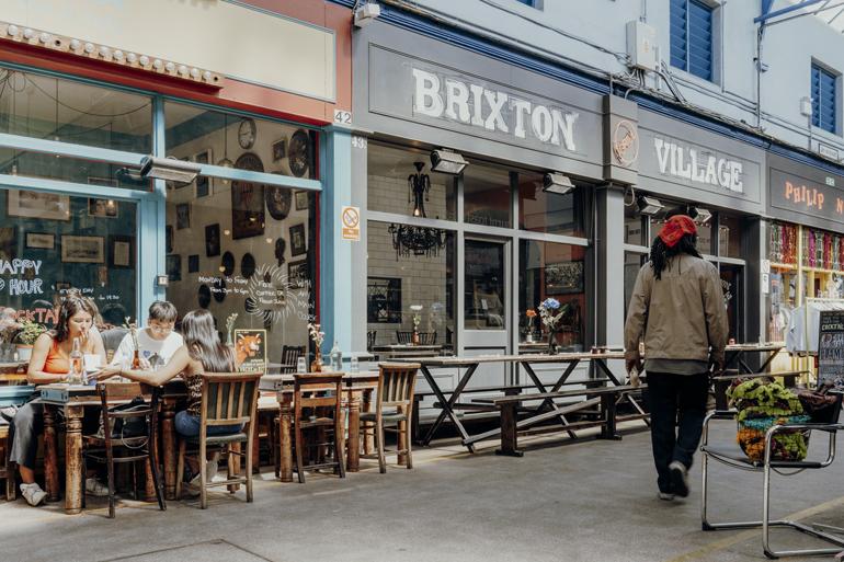 London Geheimtipps, Essen und Sehenswürdigkeiten: Eine Straße mit Cafés und Tischen die am Rand stehen.