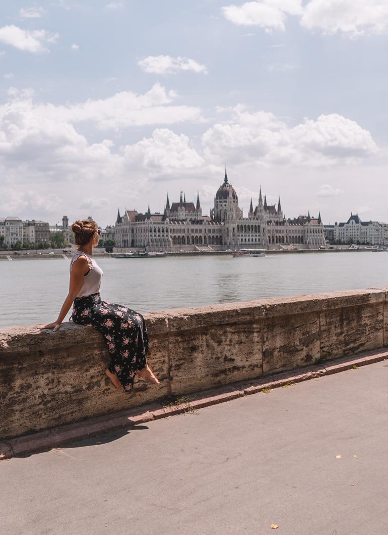 Budapest Städtetrip: Eine Frau sitz auf einer Mauer im Hintergrund ist Wasser zu sehen und ein Gebäude.