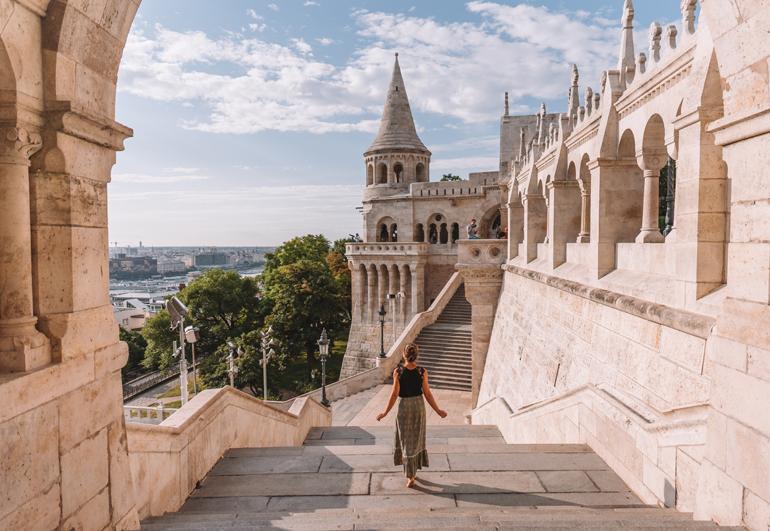 Budapest Städtetrip: Eine Frau die eine Treppe hinunter geht mit einem Gebäude im Hintergrund.