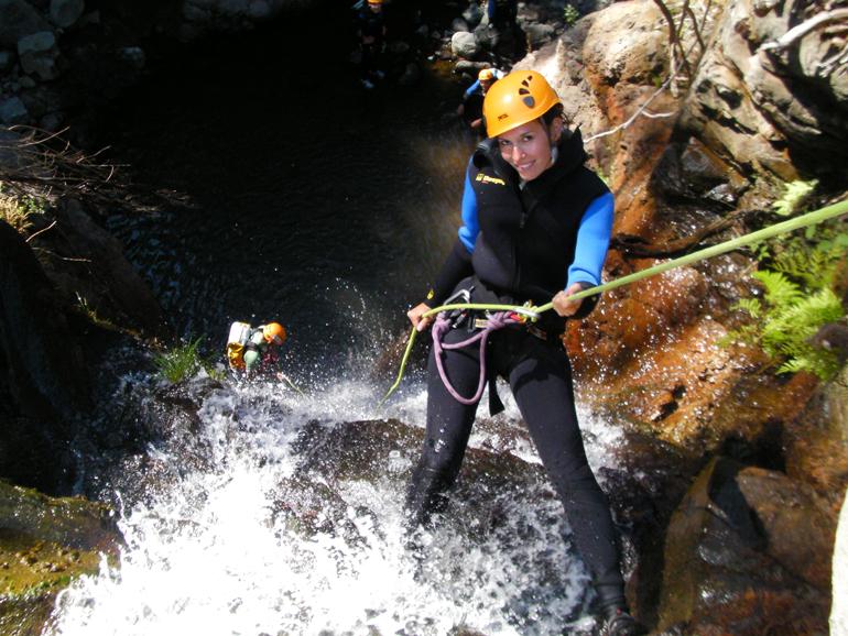 Madeira Tauchen, Surfen: Eine Frau steht angeseilt an einem Felsen im Wasser.