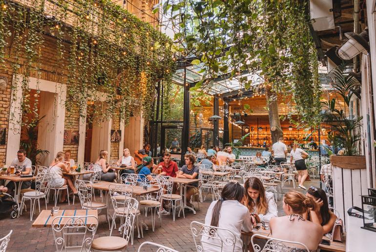 Budapest Städtetrip: Innenhof eines Restaurant mit Pflanzen die von der Decke hängen.