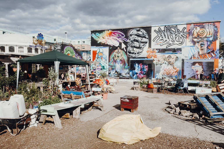 London Geheimtipps, Essen und Sehenswürdigkeiten: Ein kleiner Hinterhof mit Bänken und Graffitis in dem Wänden.