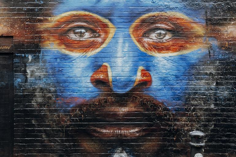 London Geheimtipps, Essen und Sehenswürdigkeiten: Eine Backsteinwand mit einem gezeichnetem Gesicht darauf.