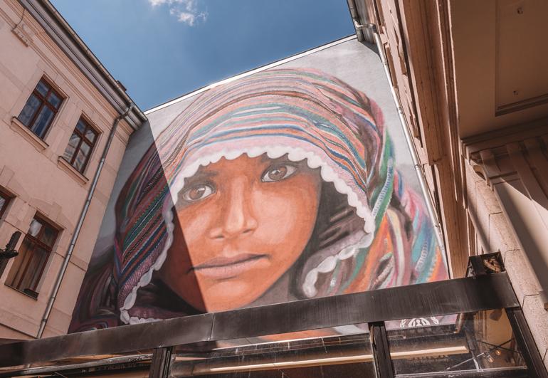 Budapest Städtetrip: Eine bemalte Wand auf der ein Gesicht mit einem Tuch zu sehen ist.