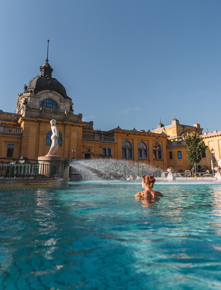 Budapest Städtetrip: Ein Schwimmbad vor einem gelben Gebäude mit einer Person darin.