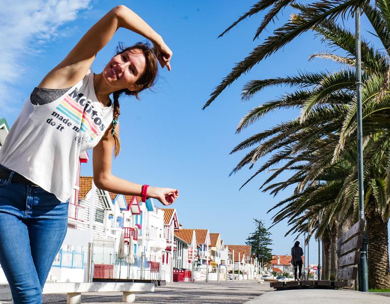 Eine Frau lehnt sich von links ins Bild, hinter ihr befinden sich blauer Himmel, bunte Häuser und Palmen.