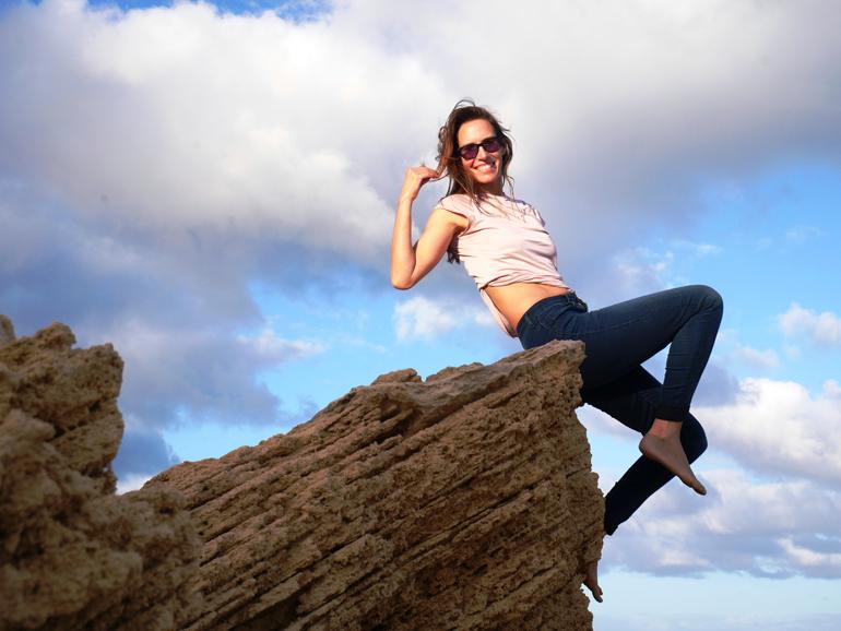Eine Frau sitzt auf einem Stein in Madeira.