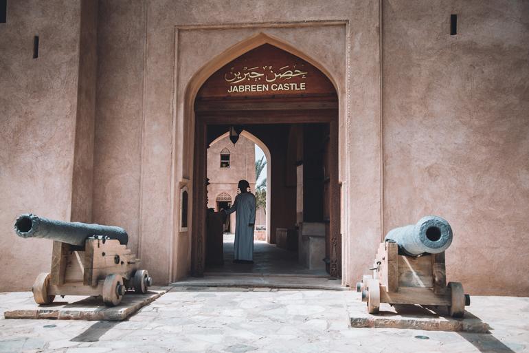 Oman Roadtrip; Reiseroute: Ein Thor zu einer Burg in der ein Mann steht.