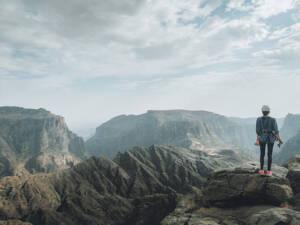 Roadtrip durch den Oman: Eine Frau von hinten, gekleidet in Kletterausrüstung, blickt auf die bergige Landschaft.