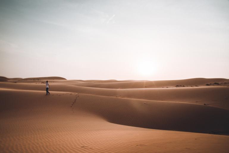Oman Roadtrip; Reiseroute: Wüstenlandschaft mit einer laufenden Person.