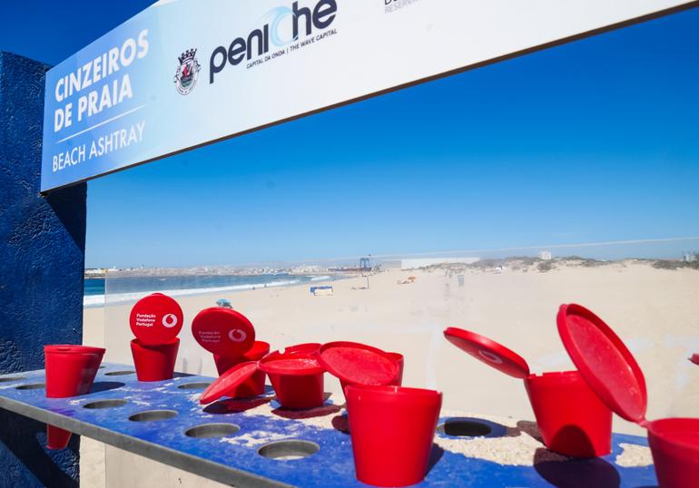 Rote Becher als Aschenbecher am Surfer Strand von Peniche Supertubos, Portugal.
