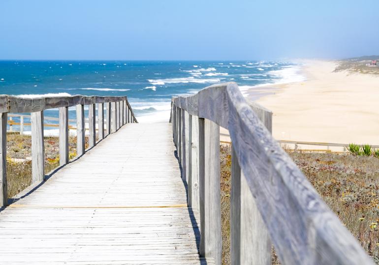 Eine Holzbrücke führt zum Strand von Sao Pedro de Moel, Portugal.