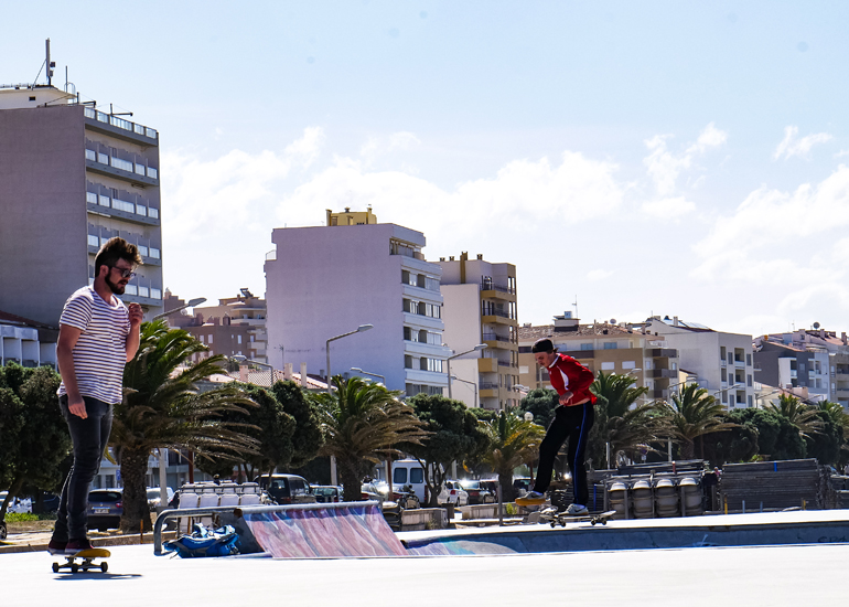 Skater auf einer Halfpipe, im Hintergrund Apartmenthäuser, in Buarcos, Portugal.