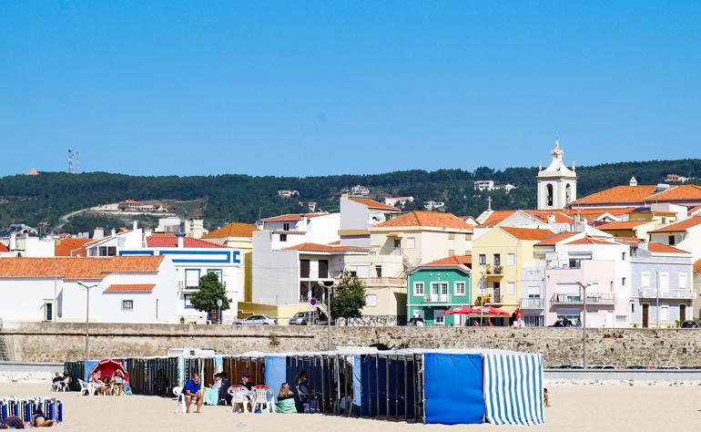 Am Strand von Buarcos in Portugal sitzen Menschen, dahinter erheben sich bunte Häuser.