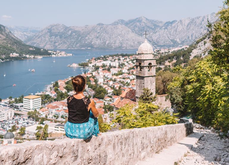 Reisetipps, Geheimtipps, Strand: Eine Frau sitzt auf einer Mauer im Hintergrund ist die Stadt zu sehen.