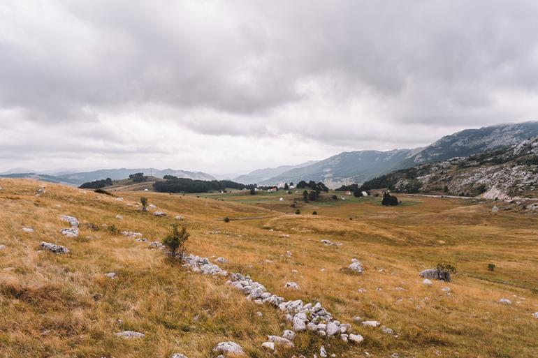 Reisetipps, Geheimtipps, Strand: Eine große Wiese mit Bergen im Hintergrund.