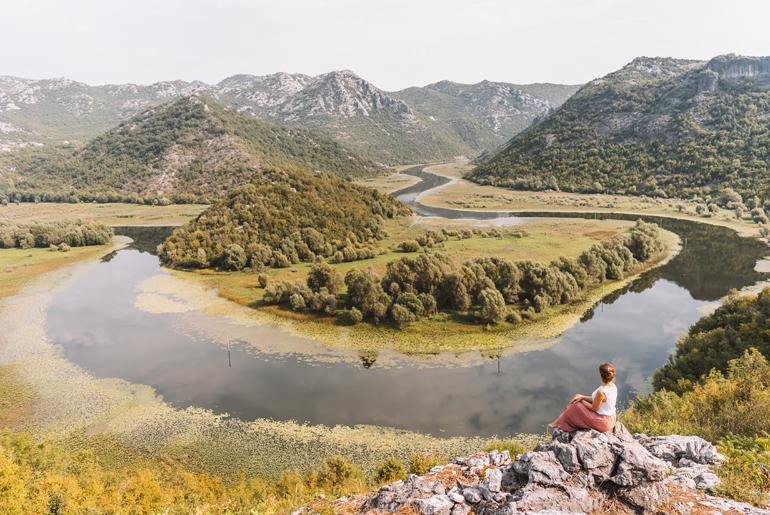 Reisetipps, Geheimtipps, Strand: Eine Frau sitzt auf einem Stein und schaut auf die Flussschleife hinunter.