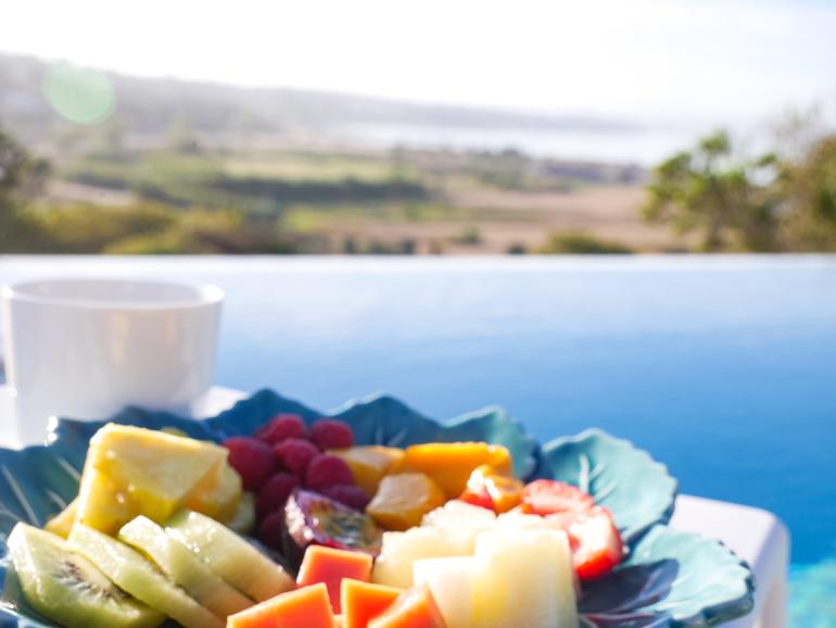 Ein Obstteller und eine Kaffeetasse mit Ausblick auf eine Landschaft.
