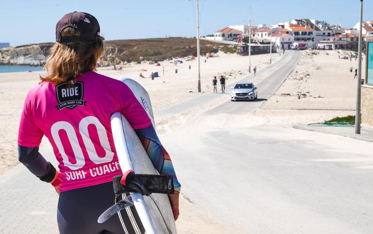 Eine Frau mit einem Surfbrett von hinten geht einen Weg entlang in Peniche, Portugal.