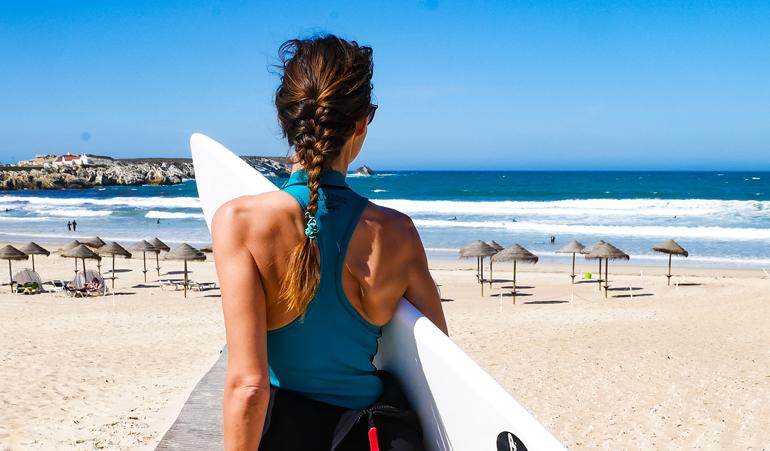 Frau mit Surfbrett von hinten am Strand von Peniche, Portugal