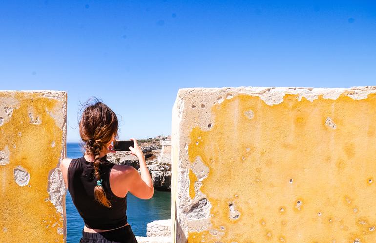 Eine Frau zwischen zwei gelben Mauern eines Forts in Peniche, Portugal.