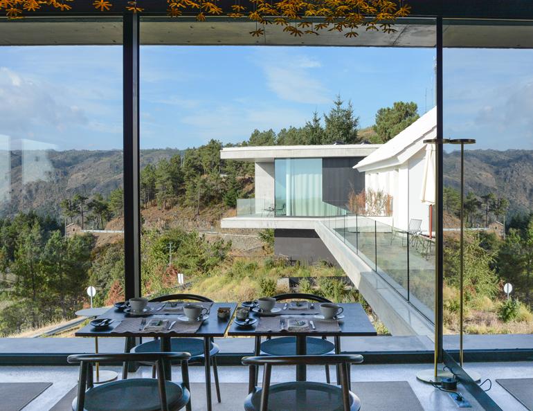 Ein modernes Haus mit einem großen Essbereich und großen Glasfenstern.