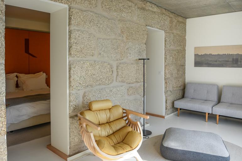 Eine Steinmauer vor der ein Sessel steht.