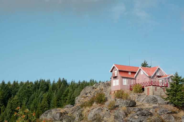 Ein rotes Haus das auf einem Berg steht.