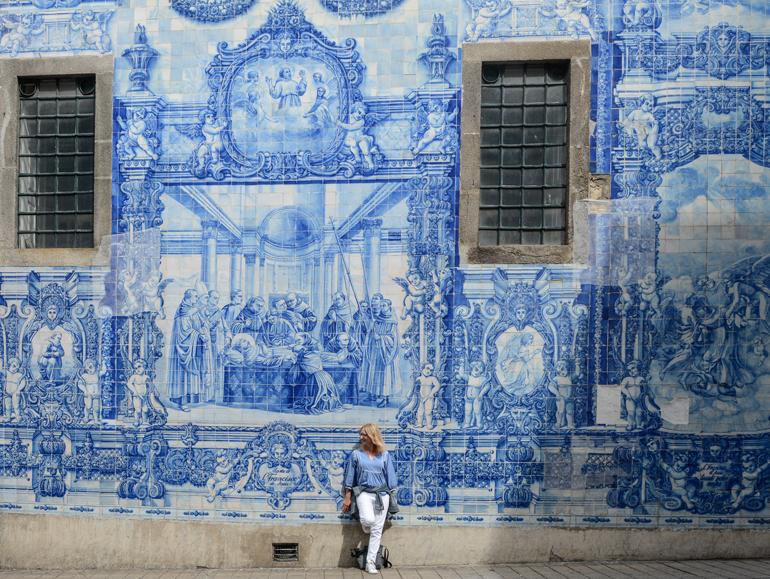 Porto Sehenswürdigkeiten: Eine Wand voller Fließen mit einer Frau davor.