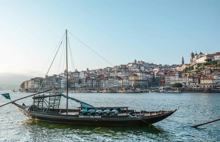 Porto Sehenswürdigkeiten: Ein Schiff das Vor der Stadt im Wasser fährt.