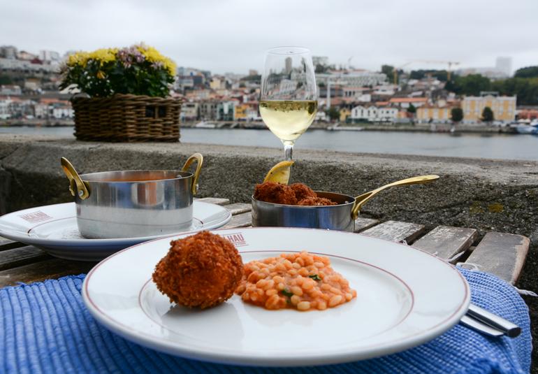 Porto Sehenswürdigkeiten: Essen und ein Weinglas stehen auf einem Tisch, im Hintergrund ist die Stadt zu sehen.