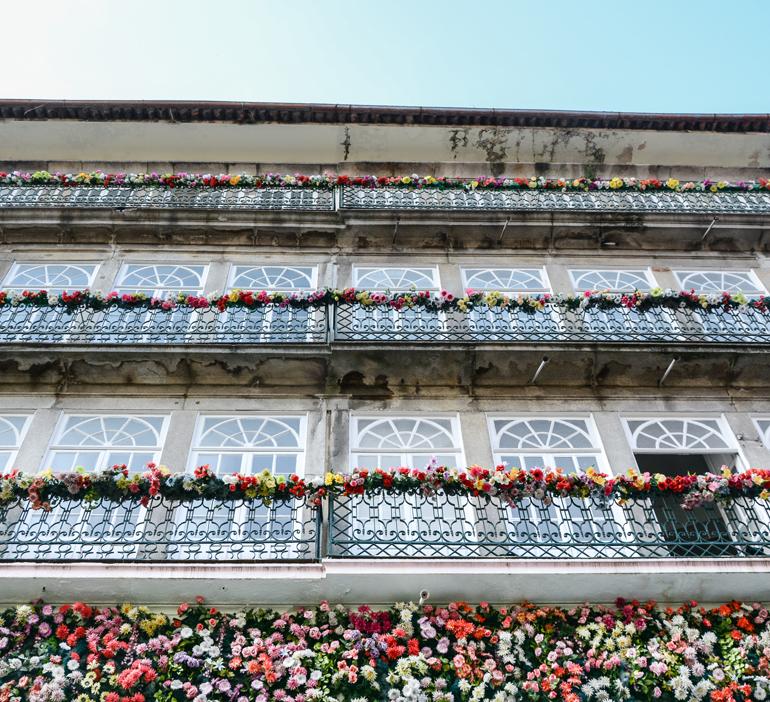 Porto Sehenswürdigkeiten: Ein Haus von unten, an dem die Balkone mit Blumen verziert sind.