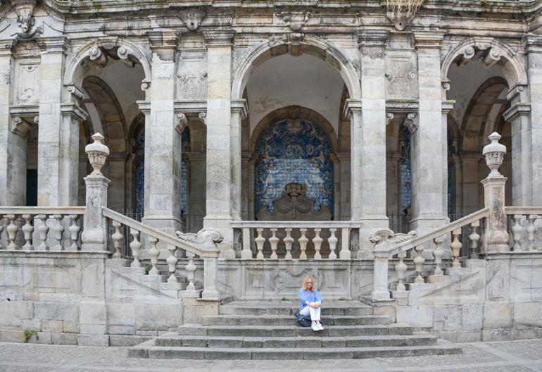 Porto Sehenswürdigkeiten: Eine Frau die vor einem altem Gebäude auf einer Treppe sitzt.