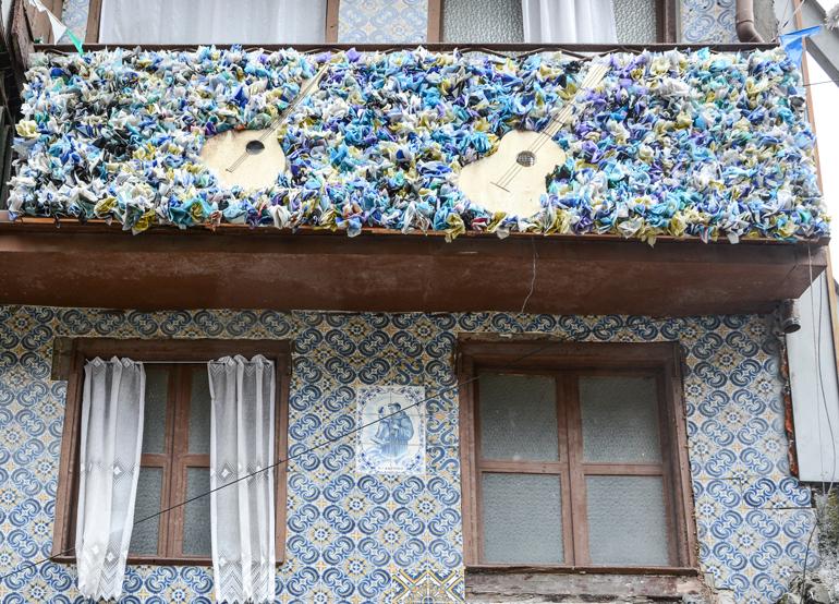 Porto Sehenswürdigkeiten: Ein Haus mit Fliesen an der Versace und einem Balkon der voller Blumen ist.