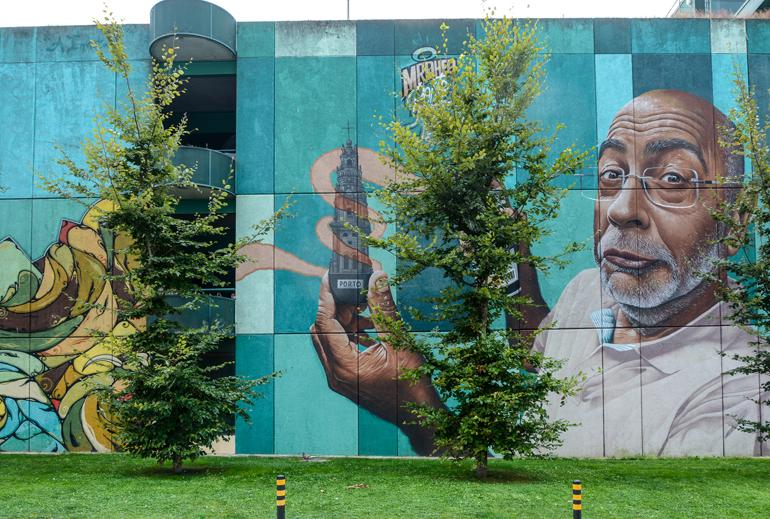 Porto Sehenswürdigkeiten: Eine große bemalte Wand Auf der ein Gesicht von einem Mann zu sehen ist der Einen Baum in der Hand hält.