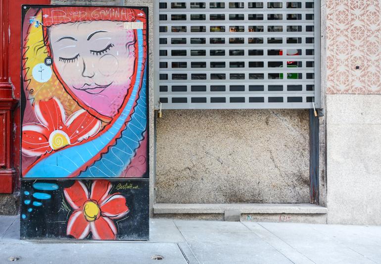 Porto Sehenswürdigkeiten: Eine bemalter Stromkaten auf dem ein Gesicht und Blumen zu sehen sind.