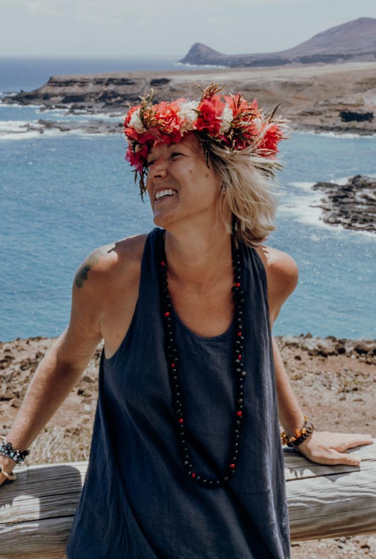 Eine Frau mit einem Blumenkranz steht vor dem Meer.